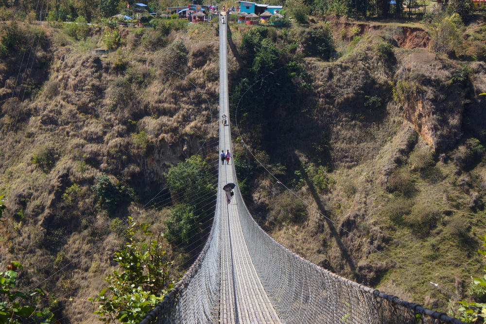 Riders crossing a suspension bridge in Nepal