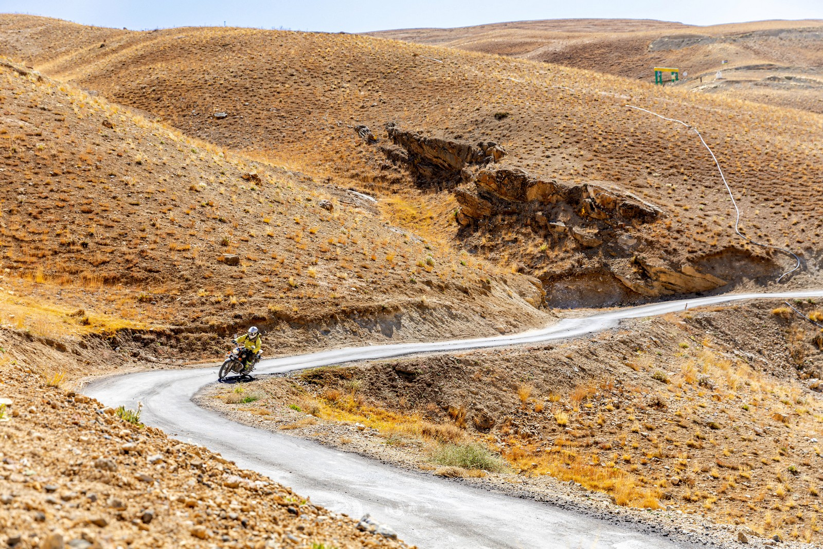 A motorcycle leans into a left hand corner high in the mountains